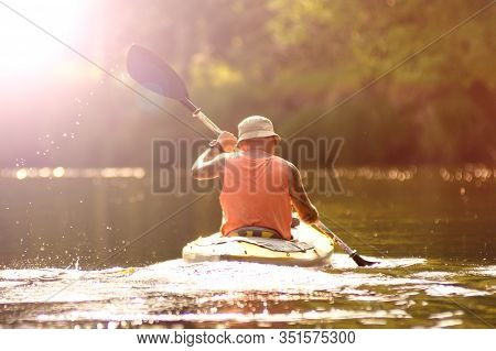 Ryazan, Russia - 06.10.2019: Back View Man With Tatoo Kayaking On River. Sunlight In The Background