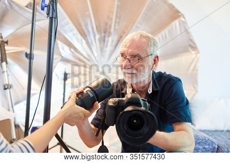 Photographer chooses a new camera lens at the photo shoot in the photo studio