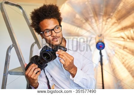 Young photographer or photo assistant at the lens cleaning in the photo studio