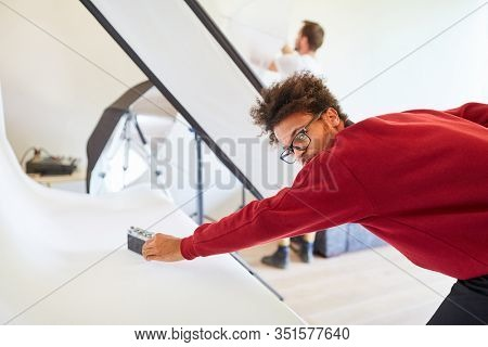 Young photographer or photo assistant in the studio prepares photoshoot