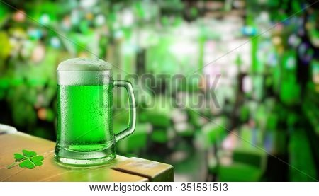 Glass of green beer stands on a table in a pub during the celebration of St. Patrick's Day. Green beer - a symbol of the feast of Saint Patrick day.
