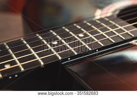 Fretboard Acoustic Guitar Of Dark Wood On A Dark Wooden Surface. The Concept Of A Musical Hobby, Chi