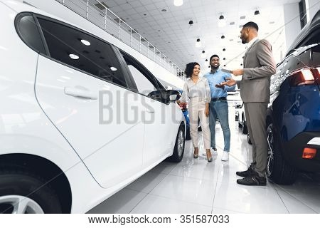 Car Sales. African American Spouses Buying New Car Choosing Auto With Seller Man In Luxury Automobil