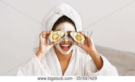 Frisky Afro Girl With Face Mask On Covering Eyes With Avocado, Face Care Concept