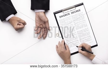Pain Of Divorce. Husband Holding Wedding Ring While Wife Signing Divorce Decree Documents Prepared B