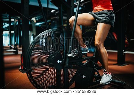 Fitness Female Using Bike For Cardio Workout At Crossfit Gym.