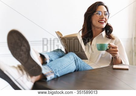 Cheerful young brunette woman reading a book while relaxing at home with cup of coffee
