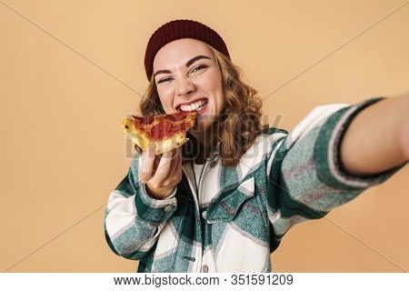 Photo of pretty happy woman in knit hat taking selfie and eating pizza isolated over beige background