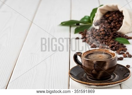 Close-up, Dark Coffee Cup Espresso With Smoke, Roasted Coffee Beans In A Burlap Sack, On White Woode