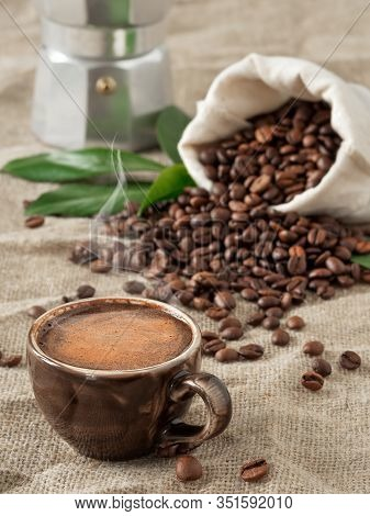 Dark Cup Of Coffee (espresso) And Coffee Beans In Burlap Sack On A Burlap Background. Close Up, Soft