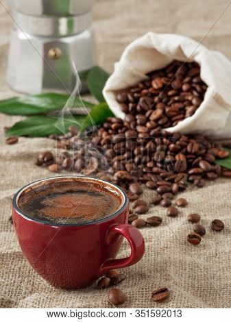 Red Cup Of Coffee With Smoke (espresso) And Coffee Beans In Burlap Sack On A Burlap Background. Clos