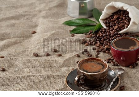 Two Colored Cups Wiht Coffee (espresso) And Coffee Beans In Burlap Sack On A Burlap Background. Clos