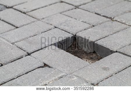 Gray Cobblestone Road Pavement With Hole Of Missed Block, Close-up Photo With Selective Soft Focus