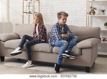 Siblings Quarrels. Offended Brother And Sister Sitting Back-to-back After Fight On Sofa At Home.