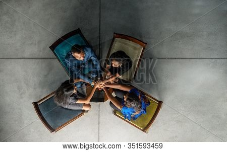 High Angle Of A Smiling Team Of Young African Businesspeople Sitting In A Huddle With Their Hands To