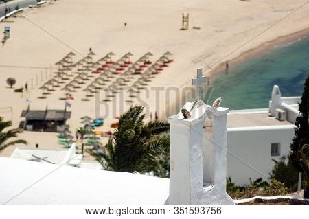 A Summers Day On The Greek Holiday Island Of Ios. A Chapel At The Top Of Cliffs Overlooking Popular