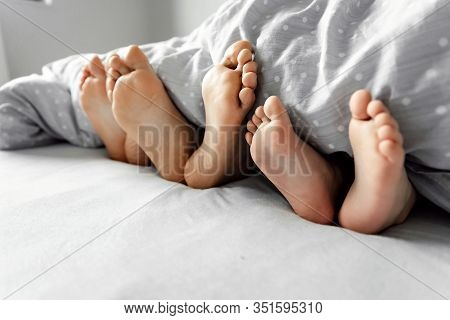 A Young Family, A Family Wakes Up In The Morning,feet On The Bed,healthy Legs Of A Young Family,fami