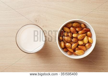 Glass of homemade vegan almond milk and water soaked almonds