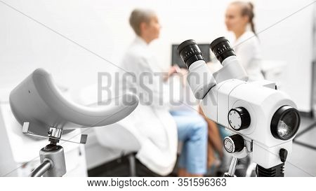 Colposcopy, Examination Of A Cervix. Colposcope Close-up, In The Background A Gynecologist And A Fem