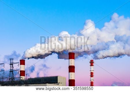 Factory Chimneys Pollute The Air, Thick Dirty Smoke, Twilight Evening Sky. Beautiful Industrial Land