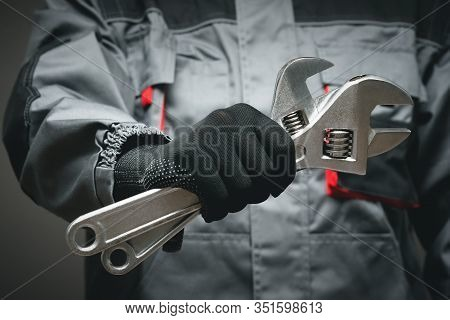 Plumber Or Car Mechanic Holding In Hand An Adjustable Wrench Close Up.