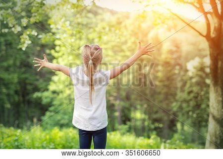 Cute Adorable Little Caucasian Child Girl Enjoy Standing In Forest During Walk At Summer Day Outdoor