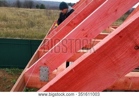 A Man Fastens Two Wooden Beams With A Self-tapping Screw, Installing Wooden Rafters On The Roof.