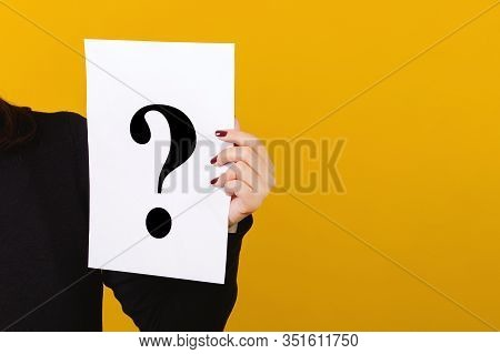Hand Holding Paper With Question Mark Over Yellow Background. Card With Question Mark Symbol. Women