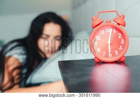 Alarm Clock On Nightstand. Asleep Woman In Early Morning In Bed. It Is Time To Waking Up. Red Alarm