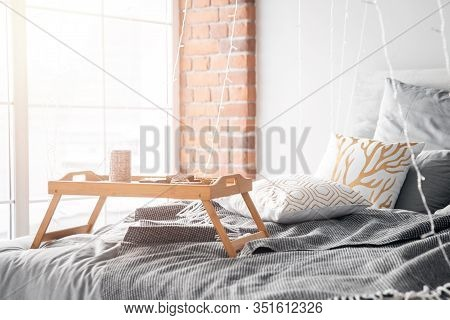 Wooden Small Breakfast Table Stands On Bed In Bedroom, Gray Sheets, Sun Shines Through Window Sunris