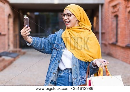 Sale, Technologies And Buying Concept - Happy Arab Muslim Woman Taking Selfie Outdoors After Shoppin