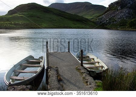 Wales, Snowdonia National Park.  A Late Summer Afternoon.  A Small Reservoir. Two Small Boats At A