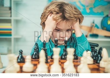 Pupil Kid Thinking About His Next Move In A Game Of Chess. Clever Concentrated And Thinking Child Wh