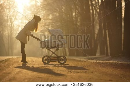 Silhouette Of Young Woman On Sunny Footpath And Looking At Child In Baby Stroller. Sunny Winter Park