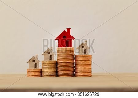 Arrange red outstanding small house or home on stacks of coins, Property investment real estate / Home loan / asset refinancing concept : depicts a homeowner or a borrower turns properties into cash.