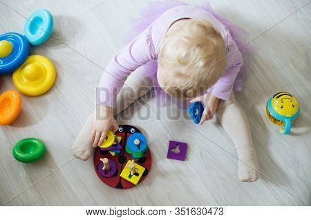 Girl Plays Toys In Living Room. Montessori Wooden Toy Folded Pyramid. Circle, Quadra, Triangle, Rect