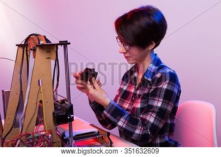 Young Female Designer Engineer Using A 3d Printer In The Laboratory And Studying A Product Prototype