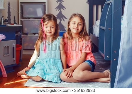 Two Cute Little Caucasian Girls Siblings Sitting On Floor At Home. Happy Smiling Friends Relationshi