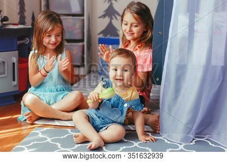 Caucasian Girls Siblings Sitting On Floor At Home And Playing With Sister Toddler. Happy Friends Rel