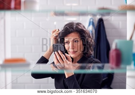 View Through Bathroom Cabinet As Businesswoman Checks Messages On Mobile Phone And Checks Hair