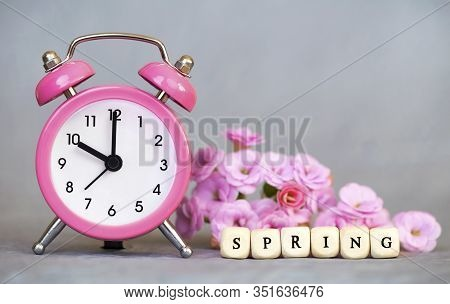 Pink Alarm Clock And Flowers On Grey Background, Spring Forward, Daylight Savings Time Concept. Copy