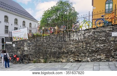 Bergen, Norway - July 22, 2018: Bright, Colorful Bicycles Are Placed On A Stone Wall. Tourists Read
