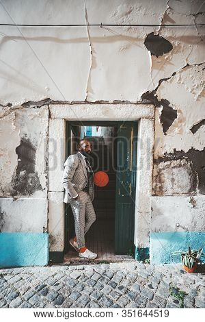 A Stylish Fancy African Man With A Beard Is Standing In The Doorway With A Basketball In Hands; Blac