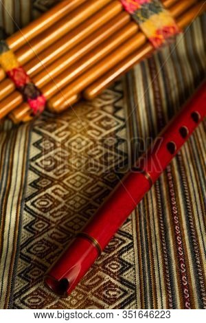Top View Of A Quena (peruvian Flute) And Pan Flute, On Colorful Peruvian Textile. Natural Light. Tra