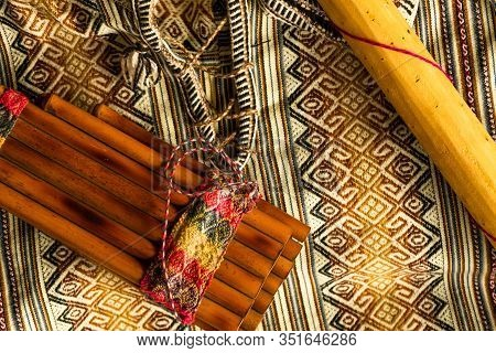 View From Above Of Peruvian Pan Flute And Rain Stick On Colorful Traditional Textile. Natural Light.
