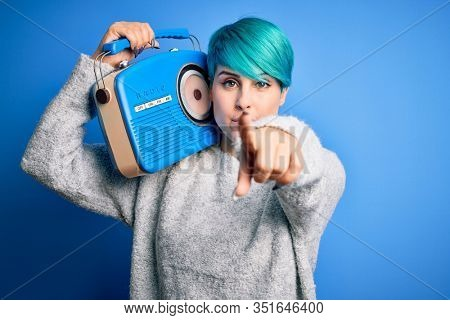 Young woman with blue fashion hair listening to music holding vintage portable radio pointing with finger to the camera and to you, hand sign, positive and confident gesture from the front