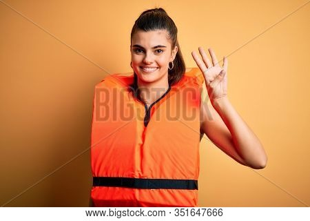 Young beautiful brunette woman wearing orange safe lifejacket over yellow background showing and pointing up with fingers number four while smiling confident and happy.