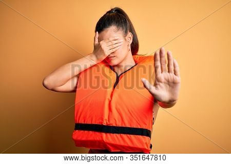 Young beautiful brunette woman wearing orange safe lifejacket over yellow background covering eyes with hands and doing stop gesture with sad and fear expression. Embarrassed and negative concept.