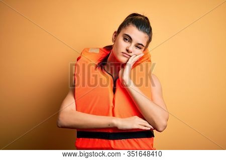 Young beautiful brunette woman wearing orange safe lifejacket over yellow background thinking looking tired and bored with depression problems with crossed arms.