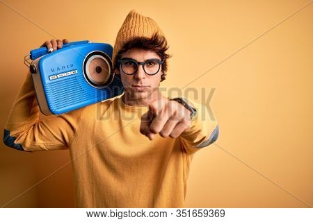Young handsome man holding vintage radio standing over isolated yellow background pointing with finger to the camera and to you, hand sign, positive and confident gesture from the front